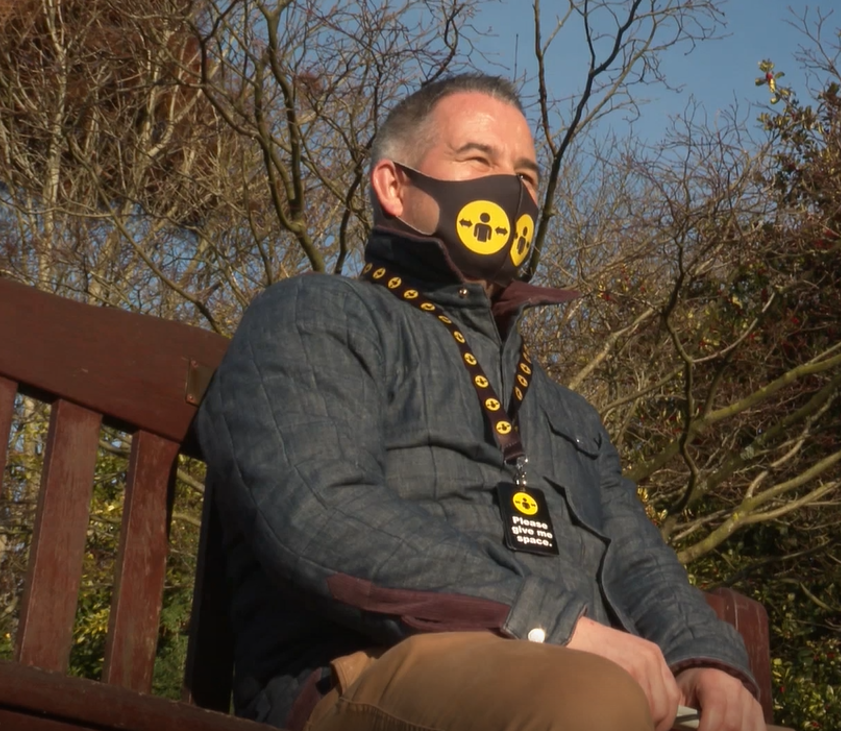Gareth Davies sitting on a bench in the park wearing Please give me space