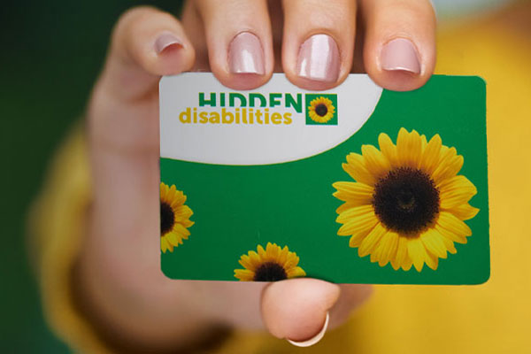 Hand holding a  green card with yellow sunflowers