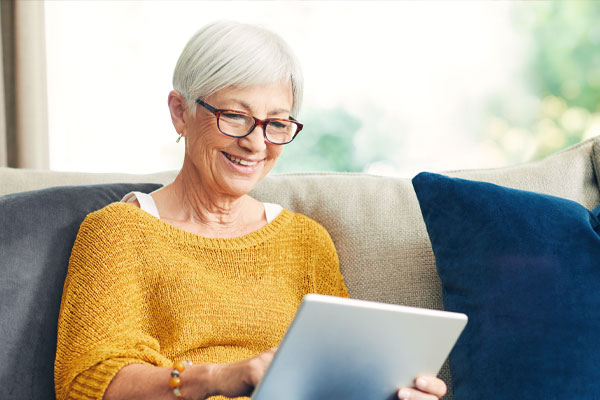 Older wooman sitting looking at a laptop
